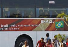 <p>Crianças do bairro de Kwa Mashu, no subúrbio pobre de Durba, correm perto do ônibus da seleção ao chegar a treino antes de jogo contra Portugal. REUTERS/Yves Herman</p>