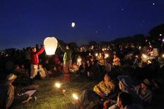 <p>Festival-goers sit around candles and set of paper lanterns at the stone circle at the Glastonbury Festival 2010 in south west England, June 23, 2010. REUTERS/Luke MacGregor</p>