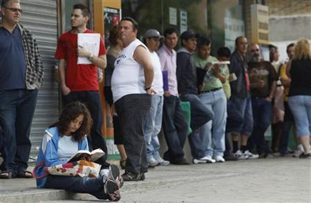 People wait in line to enter a government job center in Madrid, June 2, 2010. REUTERS/Susana Vera