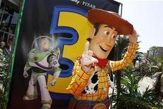"""<p>Персонаж из фильма """"История игрушек"""" Вуди стоит на фоне постера к третьей части картины, 13 июня 2010 года. Мультипликационные герои из """"Истории игрушек: Большой побег"""" по кассовым сборам в Северной Америке превзошли новые фильмы с участием Адама Сэндлера и Тома Круза. REUTERS/Danny Moloshok</p>"""