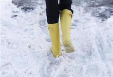 """<p>Женщина в резиновых сапогах идет по снегу в Вашингтоне 8 февраля 2010 года. У любителей музыкальных фестивалей, которые боятся в конце концов очутиться посреди грязного поля с """"севшим"""" телефоном и без возможности зарядить его, теперь есть выход - электросапоги. REUTERS/Jason Reed</p>"""