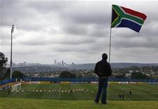 <p>Сотрудник службы охраны стоит под флагом ЮАР и наблюдает за стадионом в Йоханнесбурге, 30 мая 2010 года. Полиция ЮАР арестовала британского журналиста, при помощи которого один из болельщиков смог проникнуть в раздевалку сборной Англии по футболу, заявил комиссар национальной полиции Беки Целе. REUTERS/David Gray</p>