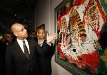 "<p>Artist and architect Saif Al-Islam Gaddafi (L), son of Libyan leader Muammar Gaddafi and chairman of the Al Qaddafi International Foundation for Charity and Development, points at his painting called ""The sun of the oasis"" as he visits ""The desert is not silent"" exhibition in Moscow, June 28, 2010. REUTERS/Sergei Karpukhin</p>"
