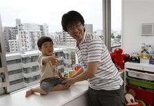 <p>Mitsuhiro Sato (R) plays with his three-year-old his son Kiichi at their home in Tokyo June 27, 2010.REUTERS/Issei Kato</p>