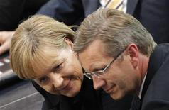 <p>Кандидат от правящей немецкой коалиции Кристиан Вульф (справа) и канцлер Германии Ангела Меркель на втором туре голосования в Рейхстаге в Берлине 30 июня 2010 года. Кандидат от правящей немецкой коалиции Кристиан Вульф в среду стал президентом Германии, однако понадобившиеся для этого три тура голосования ярко продемонстрировали разочарование политикой канцлера Ангелы Меркель. REUTERS/Tobias Schwarz</p>
