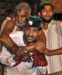 <p>Добровольцы помогают вытащить раненого мужчину из взорванного храма в Лахоре 1 июля 2010 года. Как минимум 41 человек погиб в результате трех взрывов боевиков-смертников в храме в пакистанском Лахоре, еще 120 получили ранения, сообщили власти. REUTERS/Kamran Ali</p>