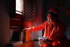"""<p>""""Живая богиня"""" Кумари рассматривает книги в своей резиденции в Патане, Непал 11 марта 2010 года. """"Власти Непала подняли ежемесячную стипендию """"живой богине"""" Кумари, чтобы на фоне инфляции индусы и буддисты по-прежнему испытывали благоговение перед девушкой. REUTERS/Shruti Shrestha</p>"""