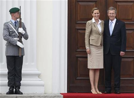 Newly sworn-in German President Christian Wulff and his wife Bettina stand on the steps of the presidential residence Bellevue palace, after a welcoming ceremony in Berlin July 2, 2010. REUTERS/Wolfgang Rattay