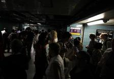 <p>People proceed through St. Andrew's subway station under emergency lighting during a power failure in downtown Toronto July 5, 2010. REUTERS/Peter Jones</p>