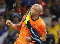 <p>Demy de Zeeuw recebe chute no rosto do uruguaio Martin Caceres durante jogo das semifinais da Copa do Mundo. O meia holandês foi levado a um hospital com suspeita de ter fraturado o maxilar durante a vitória por 3 x 2 sobre o Uruguai na terça-feira. 06/07/2010 REUTERS/Mike Hutchings</p>