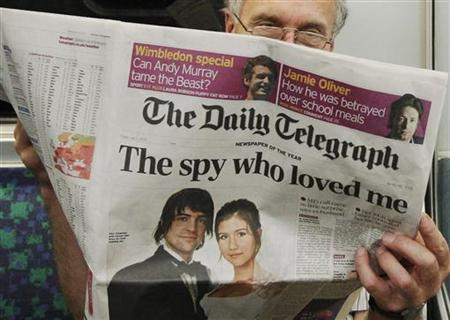A passenger reads the Daily Telegraph newspaper, featuring a front page interview with the ex-husband of accused Russian spy Anna Chapman, on the underground in London July 2, 2010. REUTERS/Luke MacGregor