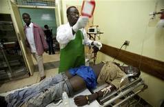 <p>Врач оказывает помощь мужчине, пострадавшему в результате терактов в Уганде, 11 июля 2010 года. По меньшей мере 64 человека погибли в результате серии взрывов в столице Уганды Кампале в воскресенье вечером во время просмотра трансляции чемпионата мира по футболу. REUTERS/Benedicte Desrus</p>