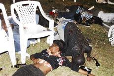 <p>Тела погибших от взрыва, прогремевшего в Кампале, лежат на земле, 11 июля 2010 года. Власти Уганды арестовали несколько человек, подозреваемых в организации двух мощных взрывов в барах столицы страны Кампалы в воскресенье, сообщил представитель правительства. REUTERS/Stringer</p>