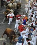 <p>Españoles corren escapándose de los toros en el Festival San Fermin, en Pamplona. Jul 13 2010. Un hombre resultó herido por asta de toro en el brazo en el penúltimo encierro de los Sanfermines, que con una duración de dos minutos y 14 segundos superó en velocidad al del día anterior y se convirtió en el más rápido de los celebrados hasta ahora. REUTERS/Vincent West</p>
