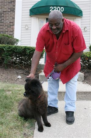 Alonzo Allen stands outside the apartment where he lives with his dog and sole companion, Ginger in Cincinnati, Ohio, July 7, 2010. Allen, 55, a former aid agency worker in Cincinnati whose benefits will run out in September, spends two days a week volunteering at the food bank in Over-the-Rhine and the other three looking for work. He said he worries about the one-bedroom apartment he rents and how he will feed his dog Ginger, who is the ''only family I have.'' REUTERS/Nick Carey