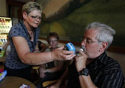 Audrey Mackenzie (L), an NHS Tayside 'Quit 4 U' smoking cessation incentive scheme co-ordinator, holds a carbon monoxide breath tester to the mouth of participant Rab Maguire during a weekly class at the Royal Victoria Hospital in Dundee, Scotland June 24, 2010. REUTERS/David Moir