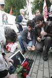 <p>Люди кладут цветы рядом с портретом убитой правозащитницы Натальи Эстимировой, 24 августа 2009 года. 15 июля 2009 года была убита правозащитница и журналистка Наталья Эстемирова REUTERS/Sergei Karpukhin</p>