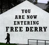 <p>A woman walks past 'Free Derry Corner' in the Bogside area of Londonderry, Northern Ireland, November 22, 2004. REUTERS/Paul McErlane</p>