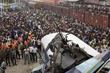 Soldiers and onlookers gather near the wreckage of train carriages at the site of an accident at Sainthia in West Bengal July 19, 2010. A speeding passenger train crashed into another waiting at Sainthia station early on Monday, killing at least 60 people in India's second major accident in as many months, officials said. REUTERS/Rupak De Chowdhuri