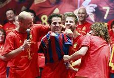 <p>Pepe Reina e Carles Puyol (dir) colocam camisa do Barcelona no colega de equipe Cesc Fabregas (centro) enquanto comemoram vitória da seleção espanhola na Copa do Mundo. O técnico do Barcelona, Pep Guardiola, afirmou nesta segunda-feira que não será fácil convencer o Arsenal a negociar Fabregas com o clube catalão. 12/07/2010 REUTERS/Andrea Comas</p>