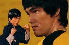 <p>Фигурка Брюса Ли стоит рядом с восковой моделью актера на выставке в Гонконге, 8 июля 2009 года. 20 июля 1973 года умер мастер боевых единоборств и актер Брюс Ли. REUTERS/Aaron Tam</p>