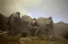 <p>U.S. Army soldiers with the 1-320 Field Artillery Regiment, 101st Airborne Division, are covered in dust as a Chinook helicopter lands outside their base during a firefight at Combat Outpost Nolen in the Arghandab Valley north of Kandahar, July 19, 2010. REUTERS/Bob Strong</p>
