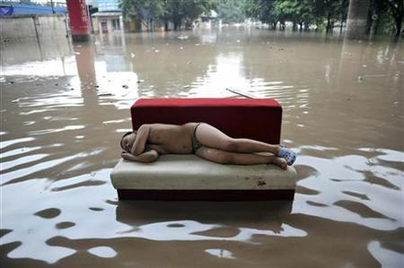 A child sleeps on a couch on a flooded street in Chongqing municipality July 20, 2010. REUTERS/Shi Tou