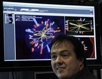 """<p>Foto de archivo de un científico frente a un monitor de computadora con las imágenes de colisiones de partículas en el Gran Colisionador de Hadrones ubicado en Meryn, Suiza, mar 30 2010. Científicos que trabajan con aceleradores de partículas en Europa y Estados Unidos dijeron el lunes que podrían estar acercándose a encontrar el esquivo bosón de Higgs, la """"partícula de Dios"""" que se cree fue crucial para formar el cosmos después del Big Bang. REUTERS/Denis Balibouse</p>"""