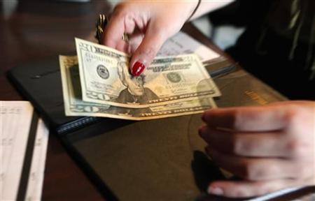 A customer pays her lunch bill at the Other Side Cafe in Boston, Massachusetts October 1, 2009. REUTERS/Jessica Rinaldi