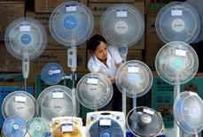 <p>Китаянка протирает вентиляторы в торговой палатке на улице в Пекине 29 мая 2003 года. Каждый новый температурный рекорд, на которые оказалось таким щедрым лето 2010 года, грозит жителям России не только тепловым ударом, но и ударом по кошельку. REUTERS/Guang Niu</p>