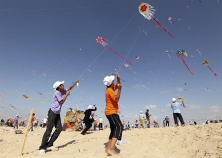 Palestinian children fly kites on the beach of Beit Lahiya in the northern Gaza Strip during a summer camp organised by the United Nations Relief and Works Agency (UNRWA) July 29, 2010. REUTERS/Mohammed Salem