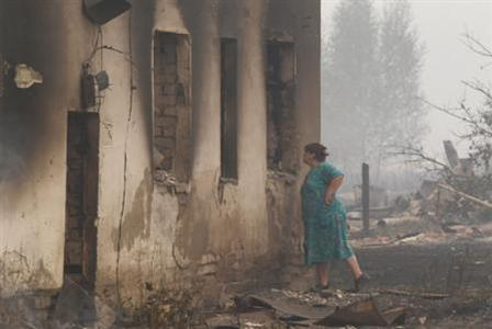 A resident looks inside while standing near the ruins of a burnt building outside the town of Vyksa, some 150 km (93 miles) southwest of the Volga city of Nizhny Novgorod, July 30, 2010. REUTERS/Mikhail Voskresensky