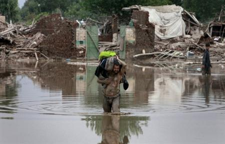 A man carries belonging on his shoulder while wading through receding flood waters in Nowshera, located in Pakistan's northwest Khyber-Pakhtunkhwa Province August 2, 2010. REUTERS/Faisal Mahmood