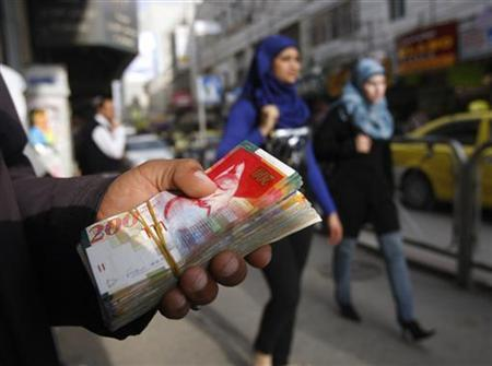 Palestinian women walk past a money changer in the West Bank city of Ramallah February 16, 2010. REUTERS/Mohamad Torokman