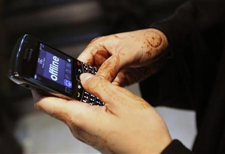 A woman uses her Blackberry mobile device at a shopping mall in Dubai August 2, 2010. REUTERS/Mosab Omar