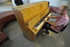 <p>O estilista britânico Wayne Hemingway toca o piano na casa de leilões Bonhams em Londres. O piano vertical Challen do estúdio Abbey Road, que foi tocado pelos Beatles, está previsto para elevar seu preço para até 150 mil libras. 02/08/2010 REUTERS/Toby Melville</p>