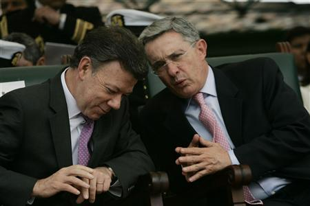 Colombia's president-elect Juan Manuel Santos speaks with President Alvaro Uribe (R) during a ceremony at Army School in Bogota August 6, 2010. Santos will succeed Uribe on August 7. REUTERS/Fredy Builes
