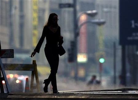 A woman walks across a street in New York's Financial district in a file photo. REUTERS/Russell Boyce