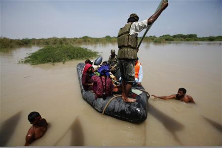 Men assist flood victims evacuate into a boat in Sukkur, located in Pakistan's Sindh province August 8, 2010. Pakistani navy boats sped across miles of flood waters on Sunday as the military took a lead role in rescuing survivors from a devastating disaster that has killed 1,600 people and left two million homeless. REUTERS/Akhtar Soomro