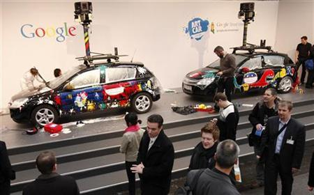 Visitors walk past painted cars with mounted cameras used for Google street view at the CeBIT computer fair in Hanover March 2, 2010. REUTERS/Christian Charisius