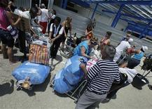 <p>Cuban American passengers unload their luggage carts after they arrive from Miami at Havana's Jose Marti International Airport August 11, 2010. REUTERS/Enrique De La Osa</p>