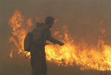 A firefighter attempts to extinguish fire outside the town of Shatura, some 68 miles southeast of Moscow, August 12, 2010. REUTERS/Sergei Karpukhin