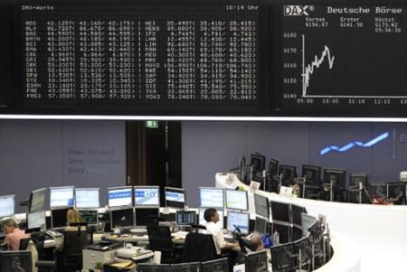 Traders work at their desks in front of the the DAX board at the Frankfurt stock exchange August 12, 2010. REUTERS/Remote/Pawel Kopczynski