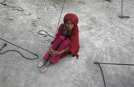 Nusrat, 9, sits on the ground at a makeshift relief camp after fleeing from a flooded village with her family in Sukkur in Pakistan's Sindh province August 14, 2010. REUTERS/Akhtar Soomro