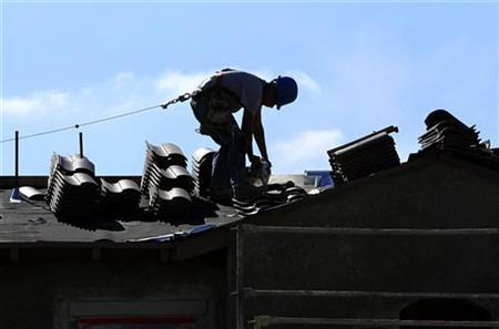 A construction worker cuts tiles as he installs a roof on a home in a new subdivision being built in San Marcos, California, April 23, 2010. REUTERS/Mike Blake
