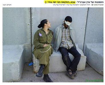 Eden Abergil poses for a photograph near Palestinian detainees in this picture taken in 2008, as seen in this screen shot of the Sachim Tumblr blog taken August 17, 2010. The former Israeli soldier said on Tuesday she saw nothing wrong in having posted the pictures of herself on Facebook posing next to handcuffed and blindfolded Palestinian detainees. REUTERS/sachim.tumblr.com/Handout