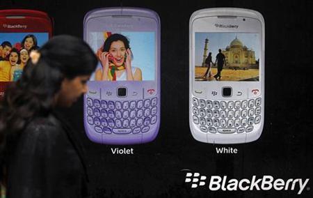 A woman walks past a Blackberry advertisement billboard in Mumbai August 17, 2010. REUTERS/Danish Siddiqui