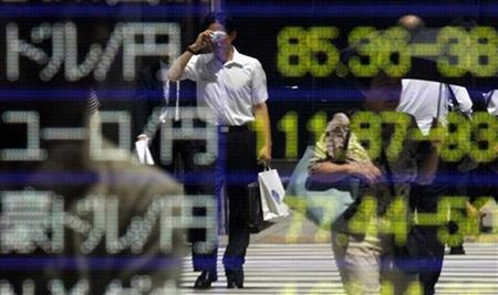 A man is reflected on an electronic board displaying exchange rates at a business district in Tokyo August 11, 2010. REUTERS/Toru Hanai
