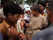 <p>Пострадавшие от наводнений жители Пакистана стоят в очереди за бесплатной едой, 18 августа 2010 года. Число людей, оставшихся без крова в результате разрушительных наводнений в Пакистане, перешагнуло за 4 миллиона, сообщила Организация объединенных наций в четверг. REUTERS/Tim Wimborne</p>