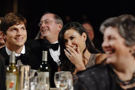Ashton Kutcher and Demi Moore laugh at President Obama's monologue at the White House Correspondents' Association Dinner in Washington, May 9, 2009. REUTERS/Jonathan Ernst